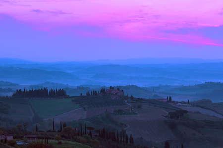 dawn - foggy morning at the Toscana with the rising sun beams. Tuscany, Italy  Stock Photo