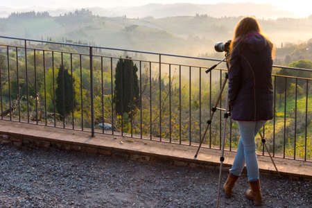 Girl making a photo shoot with view of typical Tuscan landscape and a valley with vineyards, in the province of Siena. Tuscany, Italy Stock Photo