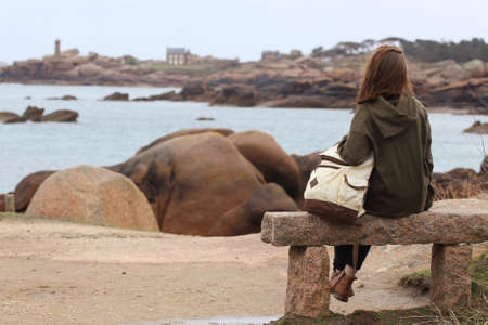 girl traveler sits on a bench near the sea and the shore at  the Tregastel, Brittany. France Reklamní fotografie - 100457743