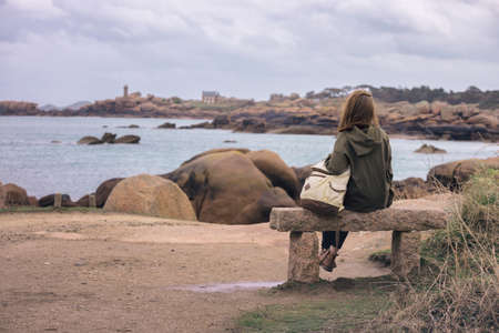 girl traveler sits on a bench near the sea and the shore at  the Tregastel, Brittany. France