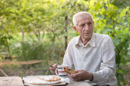 portrait of senior man sits in the garden and drinks tea with a pie Stock Photo