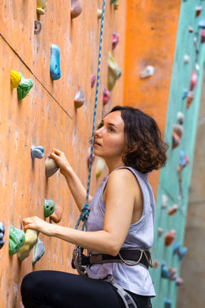 bouldering, beautiful girl climbing up the wall