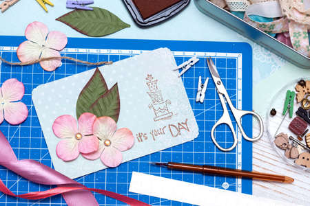scrapbook background. process of creating a postcard - Card and tools with decoration