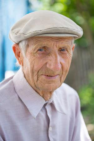 Retrato de hombre mayor sentado cerca de su casa en el pueblo Foto de archivo