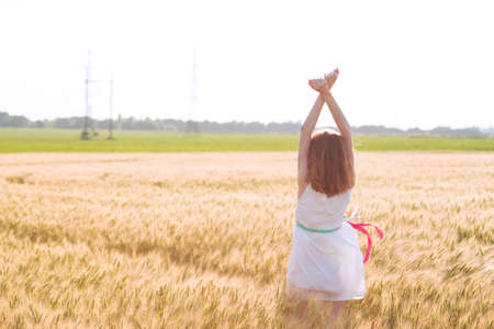 happy summer and freedom. Beautiful girl at the wheat field on a sunny day
