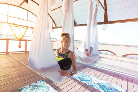 Healthy and fly Yoga Concept. happy girls are sitting in hammocks in a fly yoga class