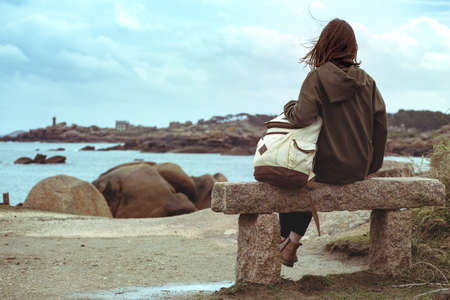 girl traveler sits on a bench near the sea and the shore at  the Tregastel, Brittany. France Reklamní fotografie
