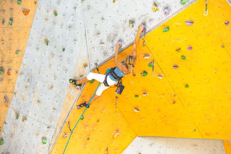 bouldering, girl climbing up the wall Stock Photo