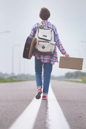 Young girl with a guitar coming along the road and hitch-hiking Stock Photo