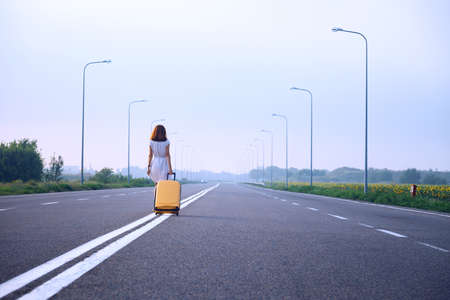 problems in the journey. the girl goes along the dividing strip with a yellow suitcase on the side of the road