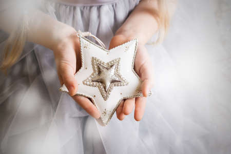 Christmas - childrens hands girl holding a star Stockfoto