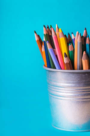 School - bucket with colourful pencils on a blue background Stock Photo