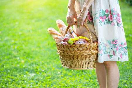 Summer - picnic in the meadow.  girl holding a basket for a picnic with baguette, wine, glasses, grapes and rolls Archivio Fotografico