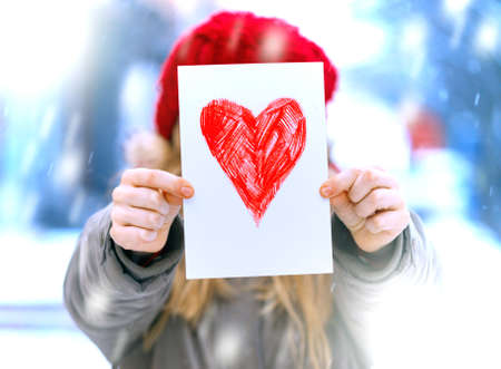 girl holding drawing with a heart on the valentines day