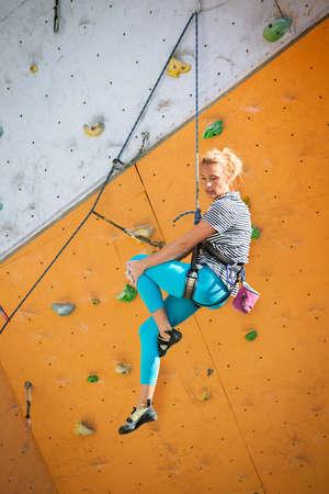 bouldering, girl climbing up the wall Stock fotó