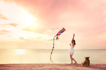 the girl launches a kite on the ocean shore during sunset. Florida