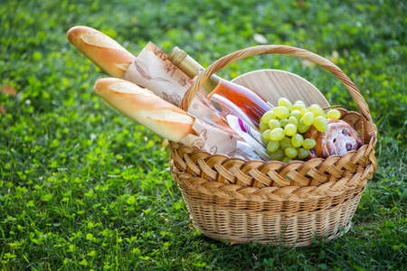 Summer - picnic in the meadow.  baguette, wine, glasses, grapes and rolls in a basket on green grass Standard-Bild