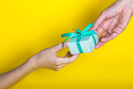 gift is given to the recipient on a yellow background. Birthday Stock Photo