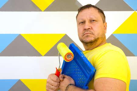 Design d'intérieur. L'homme qui travaille peint le mur en motif géométrique.