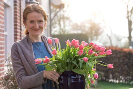 smiling happy girl holding a vase with pink tulips near with a traditional Dutch house. The Netherlands Standard-Bild
