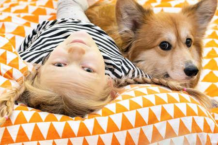 schönes blondes Mädchen und Corgi flauschig im Kinderzimmer auf dem Bett