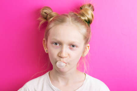 little beautiful girl blonde on a pink background looks into the camera and inflates chewing gum Banco de Imagens