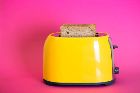 bright, fun breakfast. yellow toaster on a pink background