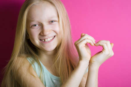 smiling girl folded hands in the shape of a heart