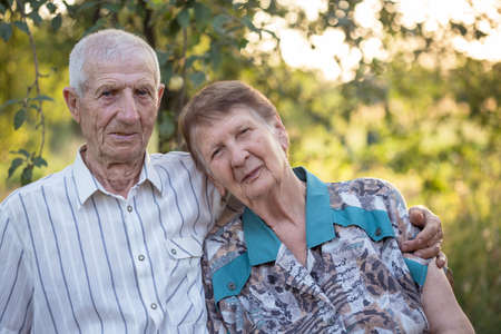 married couple. smiling grandparents. portrait of smiling senior man and senior woman at the garden. happy old age