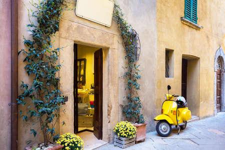 scooter de pie en la calle vacía del casco antiguo italiano. Pienza, Toscana, Italia