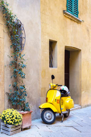 scooter standing at the empty street of old italian town. Pienza, Tuscany, Italy Banque d'images - 119745137