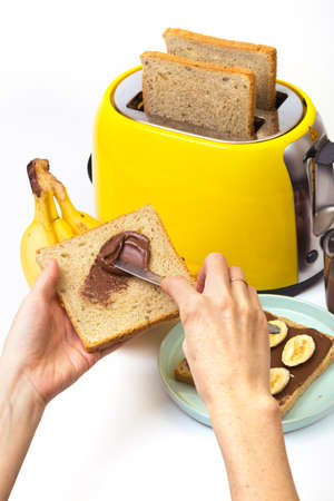 bright, fun breakfast. girl preparing toasts. yellow toaster and a cup of coffee on a white background