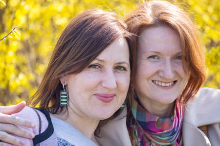 two smiling girlfriend portrait outdoors. bright spring
