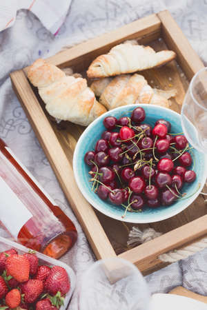 Summer - picnic in the meadow. Cheese brie, baguette, strawberry, cherry, wine, croissants and basket