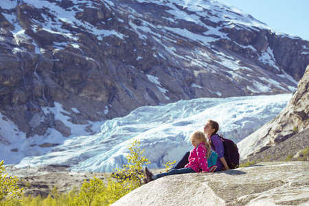 sisters hiking at the mountains and the glacier Nigardsbreen at the background. ecology and global warming