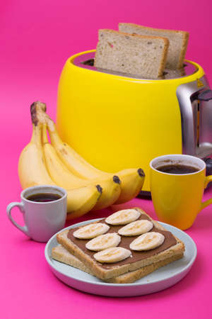bright, fun breakfast. yellow toaster and a cup of coffee on a pink background