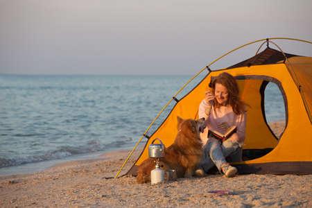 glückliches Wochenende am Meer - lächelndes Mädchen mit einem Hund in einem Zelt am Strand im Morgengrauen. Ukrainische Landschaft am Asowschen Meer, Ukraine