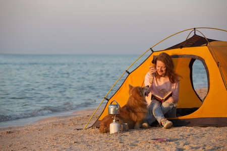 happy weekend by the sea - smiling girl with a dog in a tent on the beach at dawn. Ukrainian landscape at the Sea of Azov, Ukraine