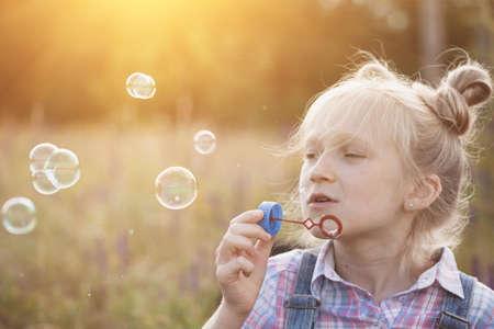 Froher Sommer - Mädchen bläst Seifenblasen im Freien