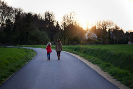 the sisters go along the empty road in the evening. village life Foto de archivo