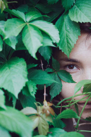 portrait of a girl in the leaves of wild grapes. natural background