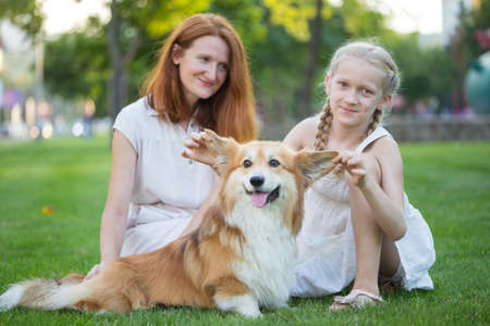 cheerful family - smiling mom and daughter and corgi fluffy  sit on the lawn Stock Photo