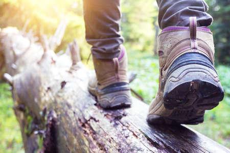 hiking boots close-up. girl tourist steps on a log