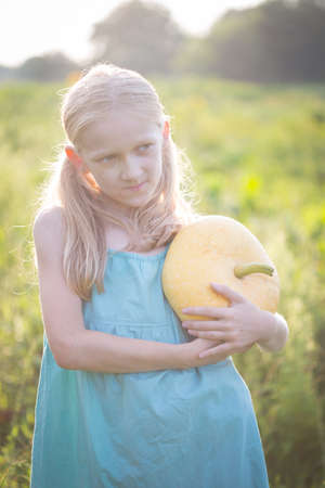 summer vacation of a little girl in the village. Fun girl with pumpkin in the garden at sunset