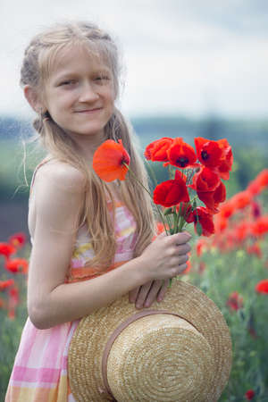 Happy little smiling girl in a hat  at the amazing field of beautiful red poppy field  in the countryside. Imagens