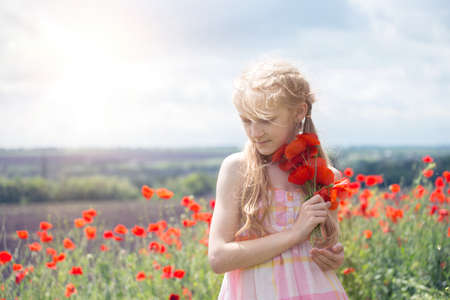Happy little smiling girl in a hat at the amazing field of beautiful red poppy field in the countryside.