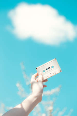 cassette in the hands of the girl against the blue sky. vintage mood 版權商用圖片