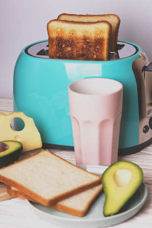 bright, fun breakfast. cyan color toaster on a wooden background Stock Photo