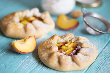 Appetizing galette with peaches on the table
