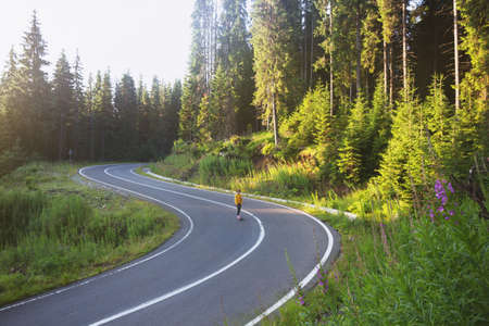 Summer Road Trip. beautiful landscape and view of a mountain road. girl rides on a skateboard at the transalpine. Romania.